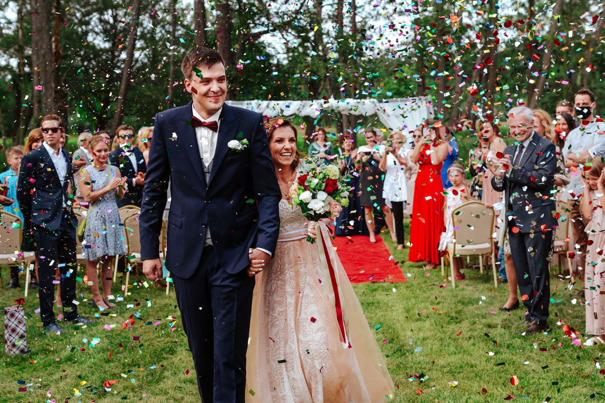 Para Młoda obsypywana confetti tuż po ceremonii ślubnej w plenerze w Dworze Many pod Warszawą